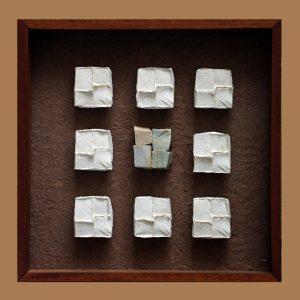 """COMPOSICIÓN RÉPLICAS - 2005 - PAPEL HECHO A MANO SOBRE MOLDE Y PIEDRA PORTUGUESA - 0,63 m x 0,63 m x 0,08 m - Primer Premio Medio Formato """"X Salón de Arte Textil """", Museo José Hernandez, 2014, Buenos Aires."""